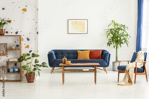 Poster above blue settee in white apartment interior with armchair, wooden table and plants. Real photo