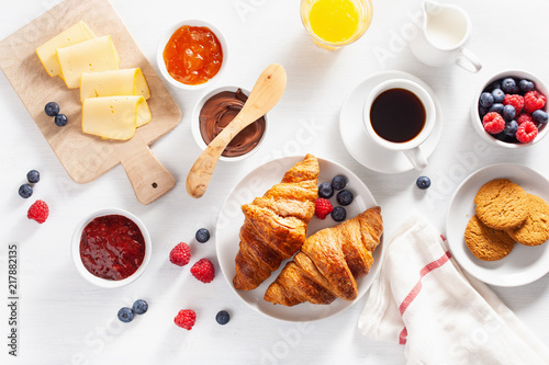Photo Continental breakfast with croissant,  jam, chocolate spread and coffee