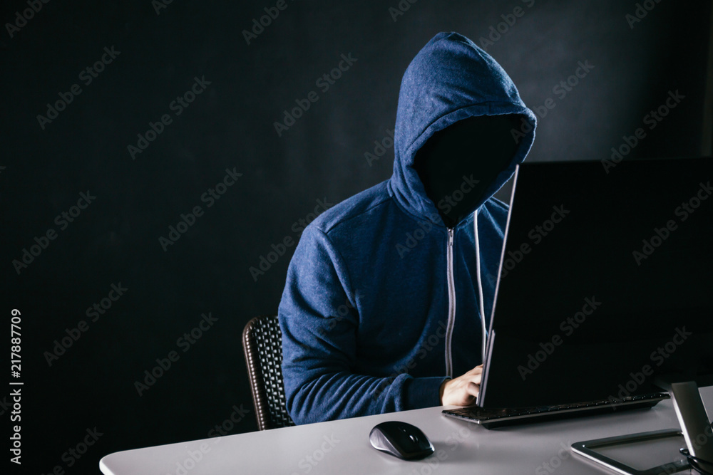 Fototapeta Anonymous and faceless hacker under hoodie using computer isolated over dark background - illegal online internet criminal concept.