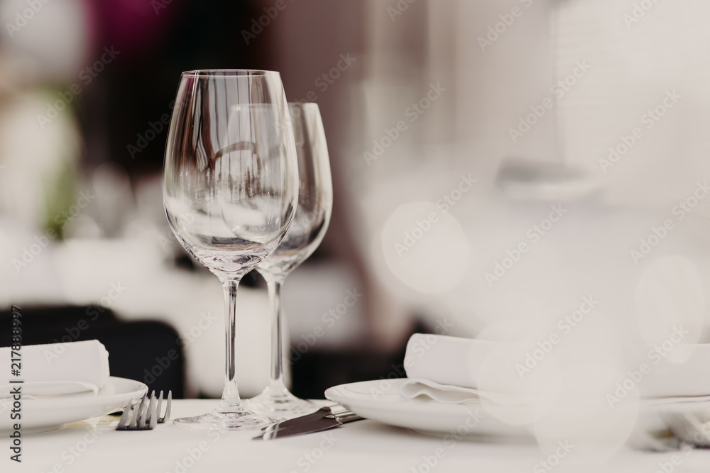 Fototapety, obrazy: Served restaurant table with cutlery and wine glasses against blurred background. Banquet table for guests. Festive event. Cozy atmosphere. Catering cafe service