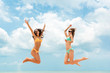 Happy woman friends in colorful bikinis jumping at the beach
