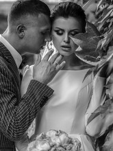 Brunette Bride Hides Her Face Behind A Green Leaf While Groom Tries To Kiss Her