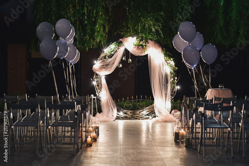 Fototapeta Shine wedding altar for newlyweds stands on the backyard decorated with balloons and greenery obraz