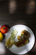 Cigar of cabbage served on white plate accompanied by slices of cucumber, sicilian lemon and tomato on rustic wooden table
