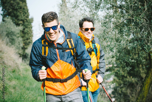 Fototapeta Two young friends who practice trekking outdoors surrounded by nature obraz