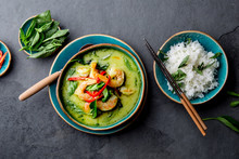 THAI SHRIMPS GREEN CURRY. Thailand Tradition Green Curry Soup With Shrimps Prawns And Coconut Milk. Green Curry In Blue Plate On Gray Background.