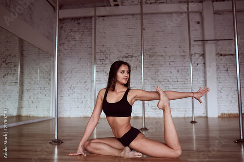 Tuinposter Gymnastiek Girl does stretching for her legs and back before pole dance training in the gym