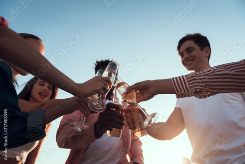 Fototapety, obrazy: Low angle outgoing ladies and smiling males clanging glasses of champagne and bottles of beer while spending time together