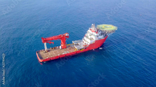 Aerial image of a Medium size red Offshore supply ship with a Helipad and a large crane