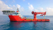 canvas print picture - Aerial image of a Medium size red Offshore supply ship with a Helipad and a large crane