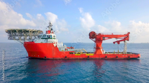 Foto Aerial image of a Medium size red Offshore supply ship with a Helipad and a larg
