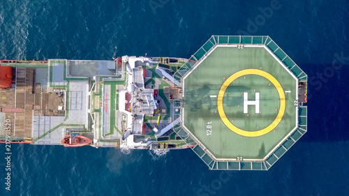 Aerial footage of a Medium size red Offshore supply ship with a Helipad and a large crane