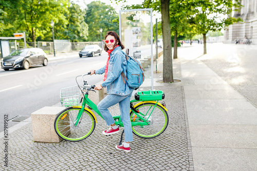 Modern woman wearing casual clothes using rental and sharing system to use Electric bicycle or E-bike on the city street
