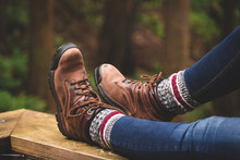 A Rustic Photo Of Hiking Boots With A Forest Background.