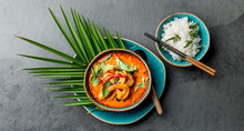 THAI SHRIMPS RED CURRY. Thailand Thai Tradition Red Curry Soup With Shrimps Prawns And Coconut Milk. Panaeng Curry In Blue Plate On Gray Background
