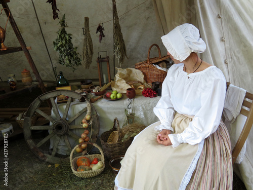 Woman in ancient dress sitting on the background of a street shop with the foodstuffs Tableau sur Toile
