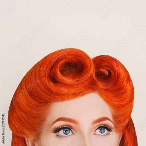 Thin eyebrow. Redhead retro model look up. Girl with perfect hairstyle. Large blue eyes with eyelashes and arrows. Beautiful smooth eyebrow. Stylish hairstyle. Work of hairdresser in salon. Look out