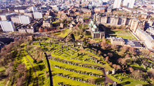 Aerial Image Of A Low Sun Casting Long Shadows In Glasgow Necropolis. Victorian Garden Cemetery Adjacent To Glasgow Cathedral.