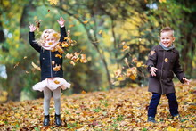 Two Children, A Boy And A Girl Throwing Leaves In An Autumn Park. The Children Are Having Fun.