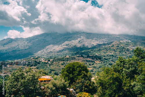 View on mountain with low hanging clouds and green trees. South Crete neat Rethymno, Greece