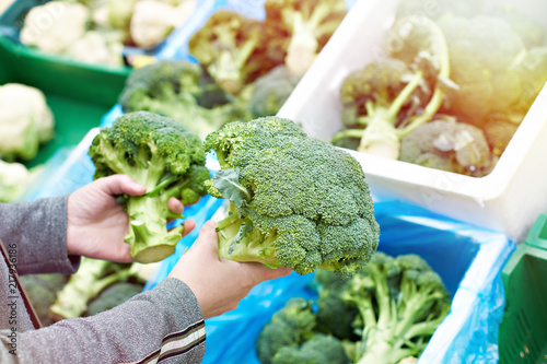 Woman buys broccoli in store