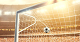 Fototapeta Sport - Photo of the ball that flies into a goal on a professional soccer stadium while the sun shines