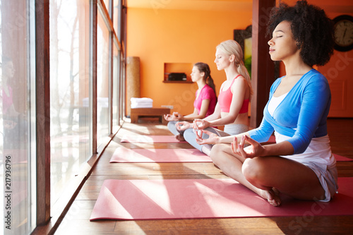 Tuinposter Ontspanning Side view of diverse confident women meditating together on yoga mats sitting near window in sunlight and relaxing