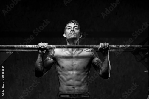 Fotografiet  Strong man with naked torso doing pull ups on horizontal bar