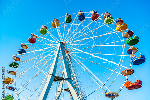 Colorful ferris wheel of the amusement park in the blue sky background