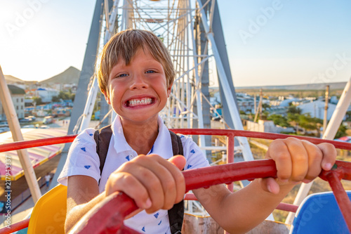 Foto  Smilling excited boy enjoying the view from ferris wheel in amusement park