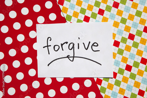 Fotografía  Forgive - word on white real paper with colorful background, relationship concep