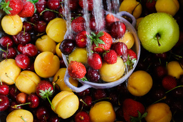 Berries and fruits under running water