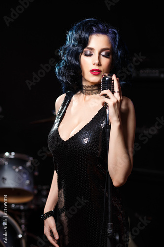 Beautiful sensual woman in black dress singing songs on the stage