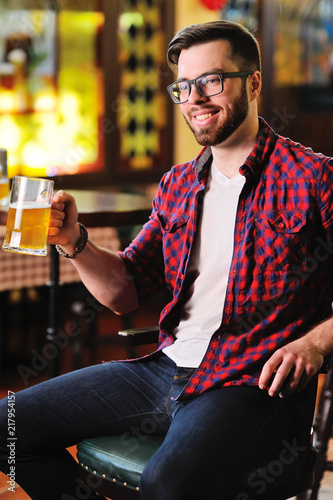 Tela Cute young man in a plaid shirt drinking beer sitting on a chair in a pub