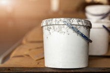Close-up Used White Dirty Plastic Paint Bucket In Room. Renovation And Repair Process Concept. Copyspace, Product Placement. Place Fot Rext