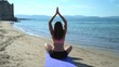 Piombino, Livorno, Italy. A girl is practicing yoga at sunrise on the beach
