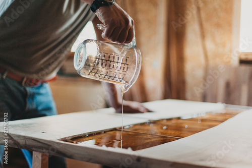 Fotografiet  Detail of Skilled Artisan Carpenter Working on a Piece of Furniture with Epoxy R