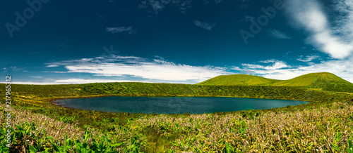 Foto op Canvas Nachtblauw Panorama of a Blue lagoon in Flores island Azores, with a green mountain and a blue sky with some clouds