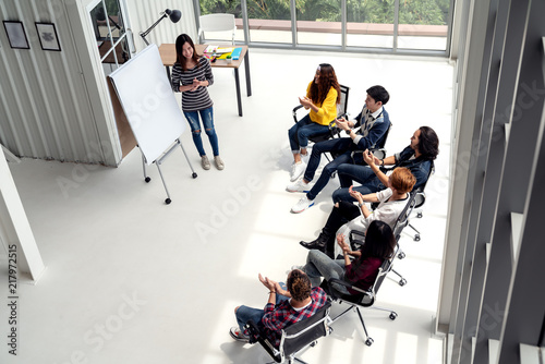 Fotografía  Young asian businesswoman explain idea to group of creative diverse team at modern office