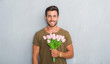 Leinwandbild Motiv Handsome young man over grey grunge wall holding flowers bouquet with a happy face standing and smiling with a confident smile showing teeth