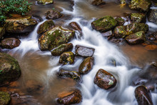 Long Exposure Scene Of Flowing Water With White Wave Through Rock River From Waterfall In Tropical Rainforest.