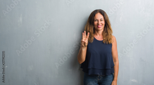 Middle age hispanic woman standing over grey grunge wall showing and pointing up with fingers number three while smiling confident and happy Wallpaper Mural