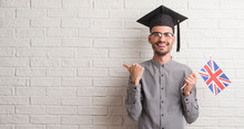 Young Adult Man Over Brick Wall Wearing Graduation Cap Holding Uk Flag Pointing And Showing With Thumb Up To The Side With Happy Face Smiling