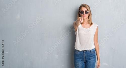 Photo  Beautiful young woman standing over grunge grey wall wearing fashion sunglasses