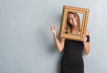 Beautiful Young Woman Over Grunge Grey Wall Holding Vintage Frame Very Happy Pointing With Hand And Finger To The Side