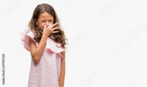 Fotografie, Tablou  Brunette hispanic girl wearing pink dress smelling something stinky and disgusting, intolerable smell, holding breath with fingers on nose