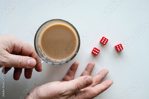Hands rolling red dice six seals, a glass mug of coffee,  isolated background, top view плакат