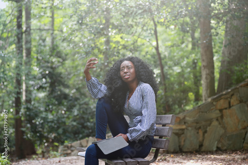 Fotografie, Obraz  Black woman reading emotive book in park
