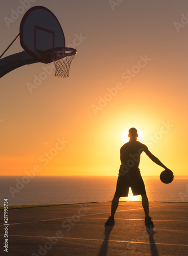 Fotografie, Obraz  Basketball player dribbling a ball at sunset. Silhouette