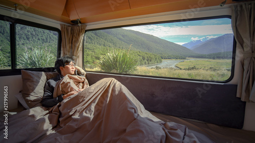 Carta da parati Young Asian man staying in the blanket looking at mountain scenery through the window in camper van in the morning